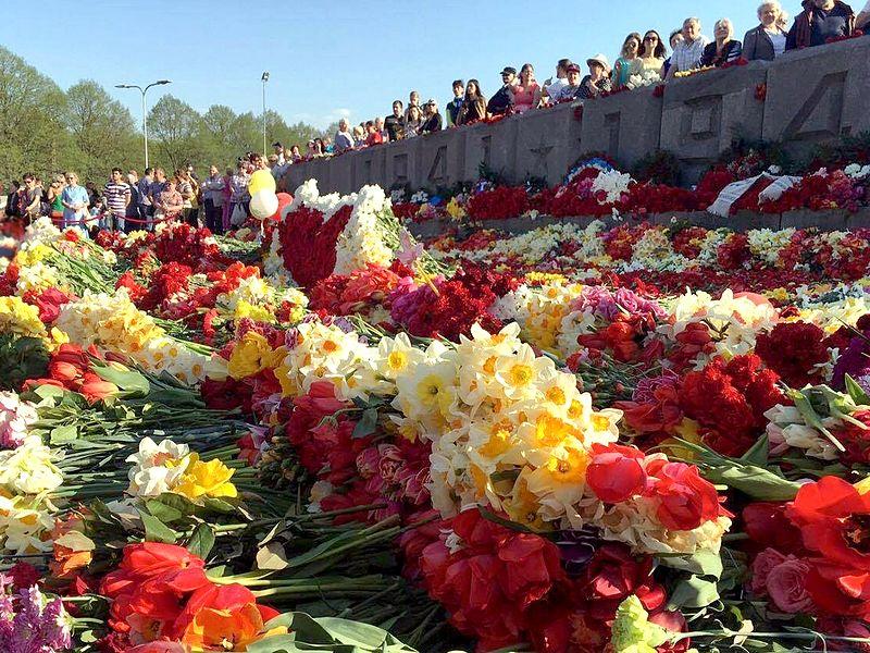 """Monumento per la Vittoria dell'Armata Rossa. Riga, 9 maggio 2016, alcuni cittadini celebrano il controverso День Победы, cioé la vittoria sovietica sui nazisti del 9 maggio 1945 che mise fine alla """"Grande Guerra Patriottica""""  (Wikipedia.ru)"""